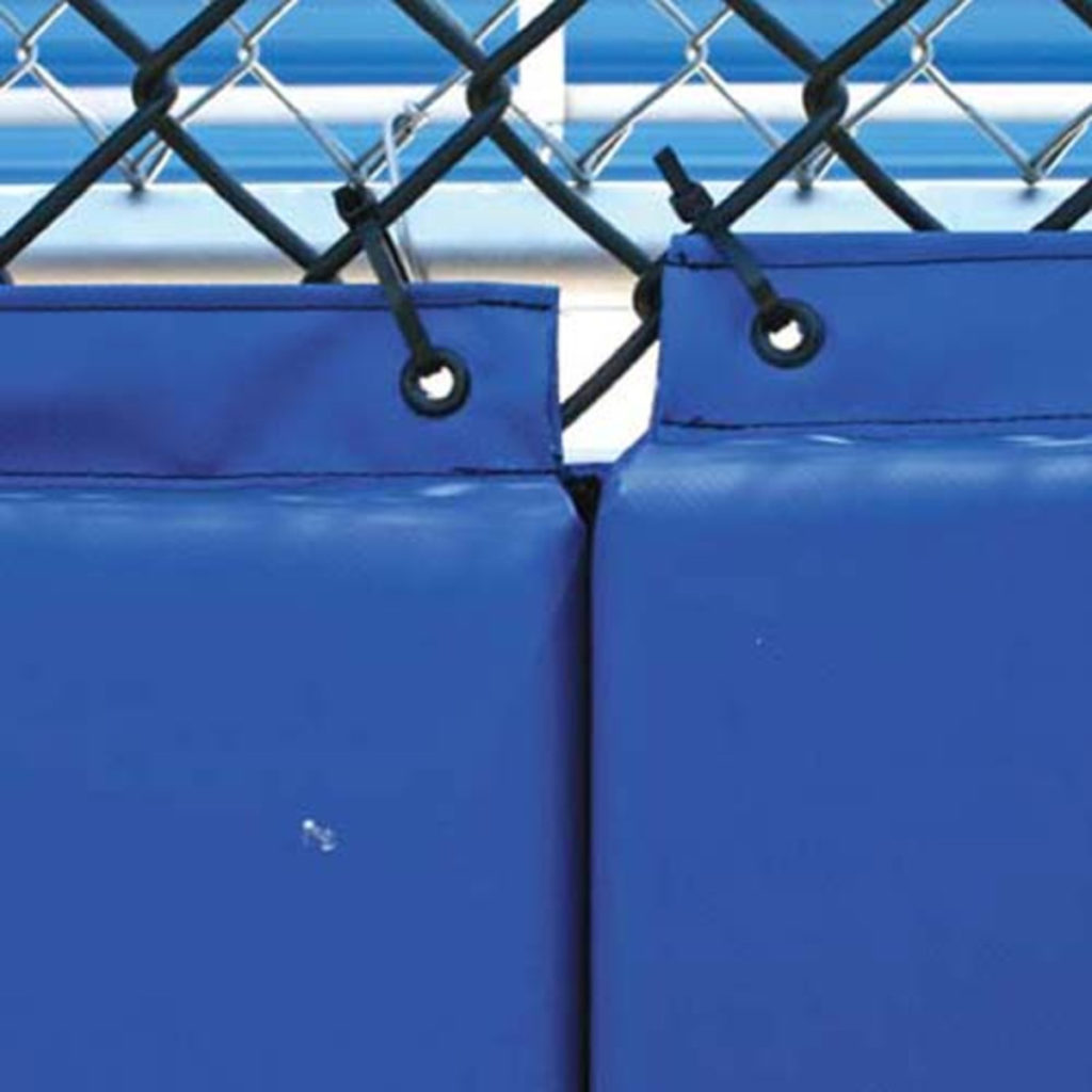 Backstop Padding with grommets attached to a baseball field fence